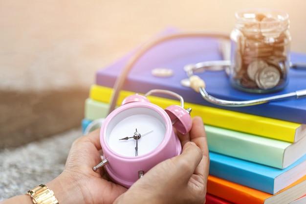 Fermer un réveil rose vintage entre les mains d'une femme. Photo Premium