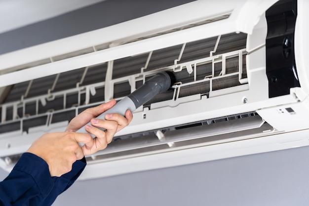 Fermer le service technique à l'aide d'un aspirateur pour nettoyer le climatiseur Photo Premium