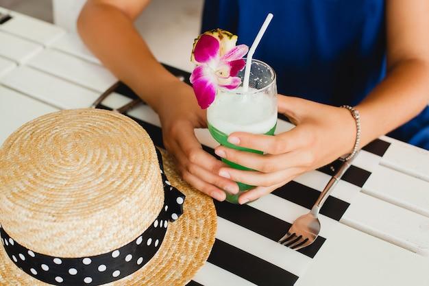 Fermer La Vue D'en Haut Des Mains De Jolie Jeune Femme Avec Chapeau De Paille, Boire Un Cocktail D'alcool Tropical En Vacances D'été Assis Table Au Bar Photo gratuit