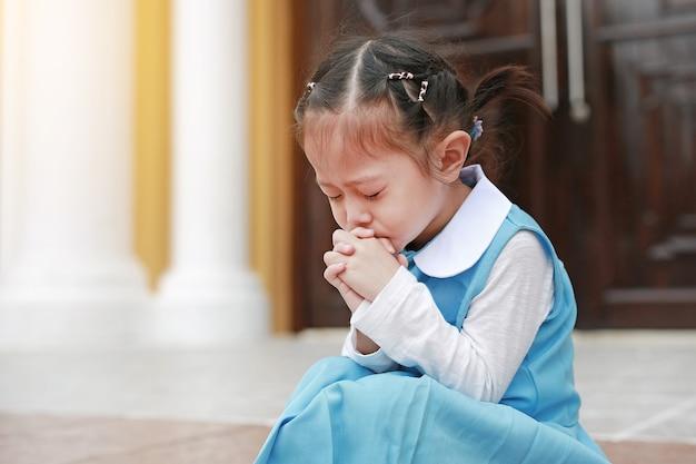 Fermer les yeux petite fille asiatique en uniforme étudiant en prière. spiritualité et religion Photo Premium