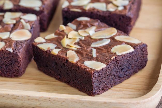 Fermez la garniture de brownies au chocolat noir maison avec des tranches d'amandes et sur une assiette en bois. Photo Premium