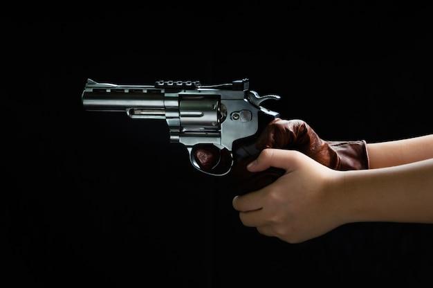 Fermez les images du pistolet dans sa main prêt à tirer. Photo Premium