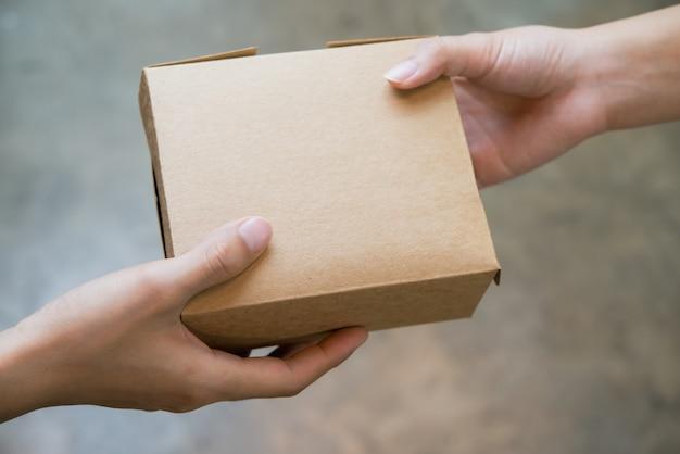 Fermez les mains en passant et recevant le paquet de petite boîte brune. Photo Premium