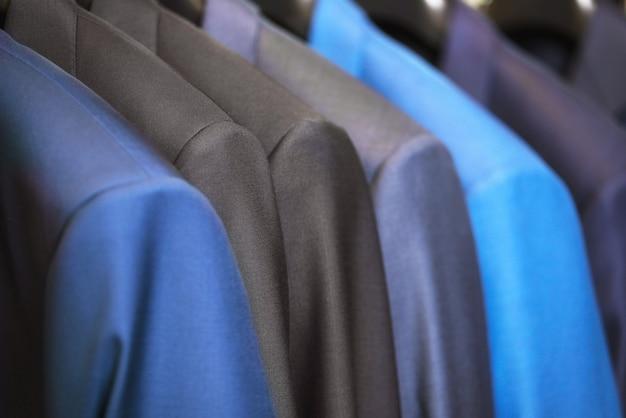 Fermez-vous dans une rangée de costumes de luxe, accrochés dans un placard. Photo Premium