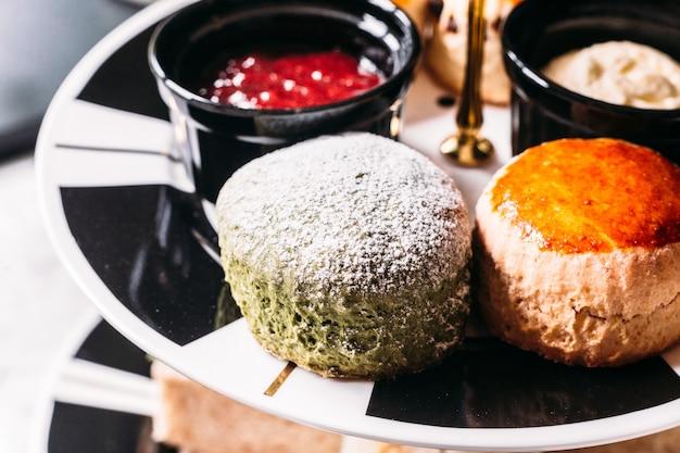 Fermez-vous avec du glaçage au thé vert et du scone ordinaire sur une plaque de couleur noir et blanc. Photo Premium