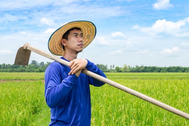 Un fermier asiatique debout dans une houe regarde le ciel avec espoir. voir un avenir frais Photo Premium