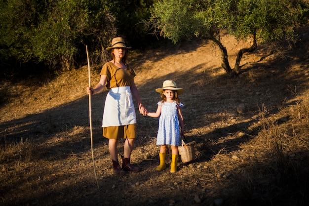 Fermière tenant la main de sa fille dans le champ Photo gratuit