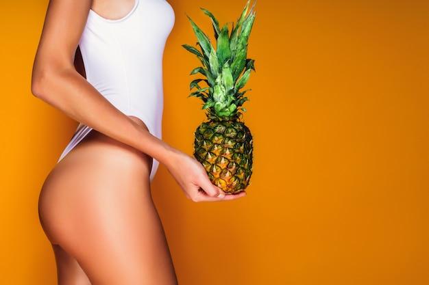Fesses Féminines, Cul Sexy. Jeune Femme Sportive Tenant Un Ananas à La Main. Photo Premium