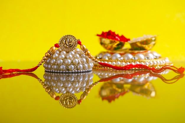 Festival indien raksha bandhan, rakhi avec des grains de riz, kumkum sur une assiette décorative, un bracelet indien traditionnel Photo Premium