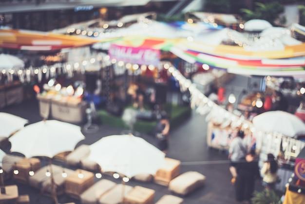Festival de marché de nuit floue gens marchant sur la route Photo Premium
