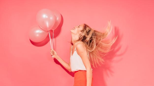 Fêtarde posant avec des ballons Photo gratuit