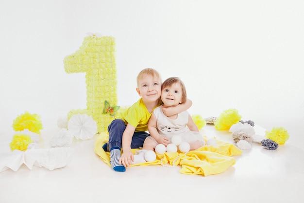 Fête D'anniversaire: Fille Et Garçon Assis Par Terre Parmi La Décoration: Numéros 1, Fleurs Artificielles Et Boules Blanches Photo Premium