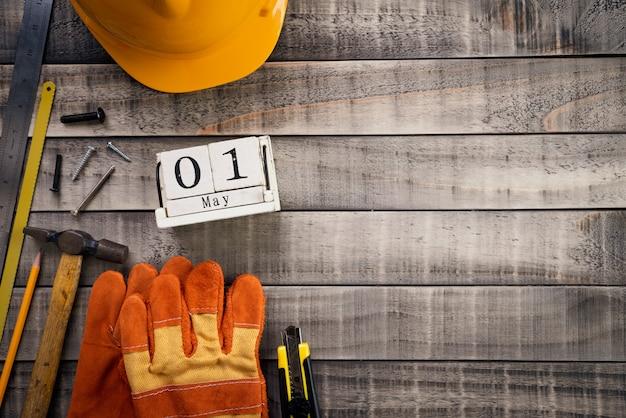 Fête du travail, calendrier de bloc en bois avec de nombreux outils pratiques sur fond en bois Photo Premium