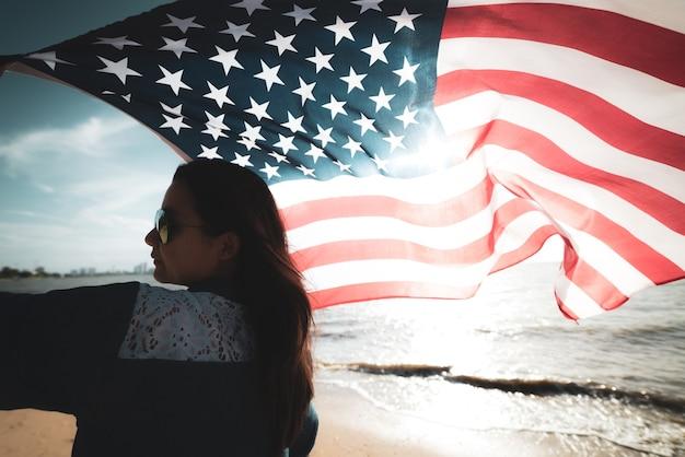 Fête de l'indépendance des états-unis, le 4 juillet. femme tenant le drapeau des états-unis d'amérique sur la plage. Photo Premium