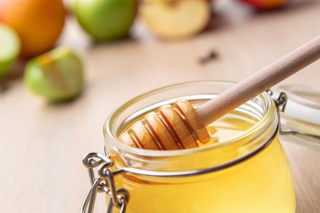 Fête juive de rosh hashana avec du miel et des pommes sur une table en bois. Photo Premium