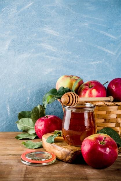 Fête juive rosh hashanah ou concept de fête de pomme, avec pommes rouges, feuilles de pomme et miel en pot Photo Premium