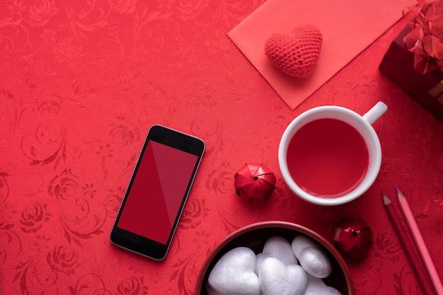 Fête de la saint-valentin avec écran blanc sur smartphone, lettre, boîte-cadeau. Photo Premium