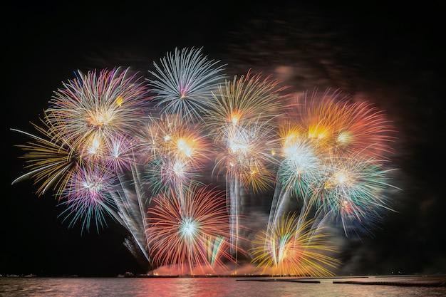 Feu d'artifice multicolore fantastique explosant pour la célébration du grand bateau au-dessus de la mer Photo Premium