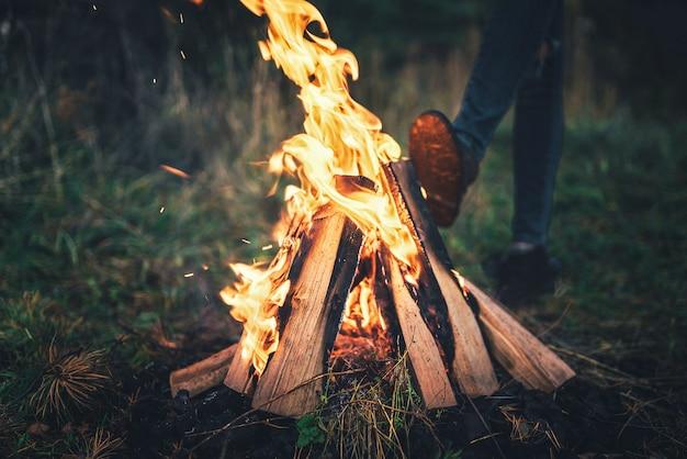 Un feu de joie dans la forêt avec une fille se réchauffant derrière. Photo Premium