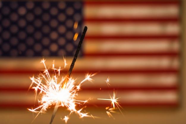 Feu de sparkler contre le drapeau américain défocalisé Photo gratuit
