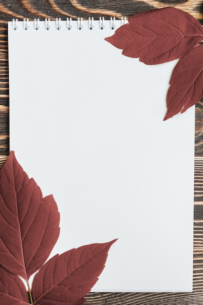 Feuille d'automne avec une feuille blanche sur une table en bois Photo Premium