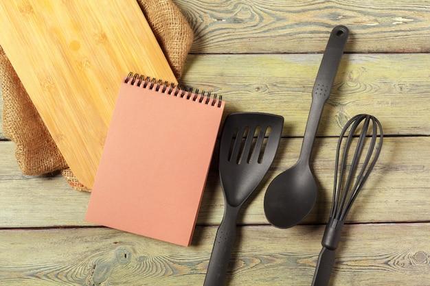Feuille blanche de bloc-notes ouvert et d'ustensiles de cuisine sur la table avec une nappe, espace de copie Photo Premium