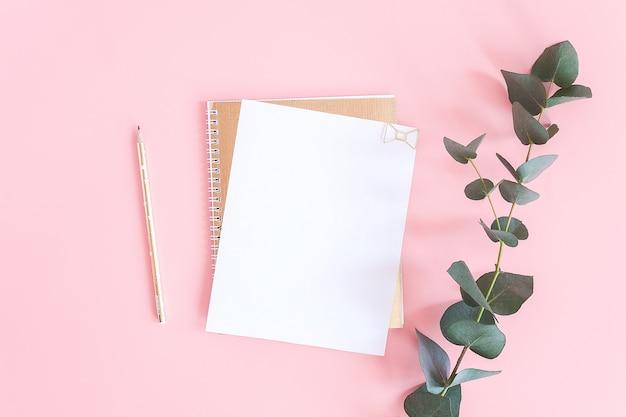 Feuille Blanche Vierge Sur Bloc-notes En Spirale Dorée Avec Trombone Coeur, Crayon Et Branche Verte D'eucalyptus Sur Fond Pastel Rose. Photo Premium