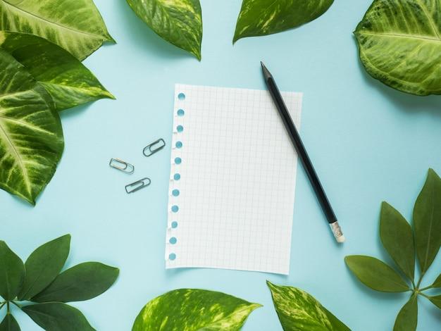 Feuille de bloc-notes avec un crayon au centre sur fond bleu avec des feuilles vertes Photo Premium