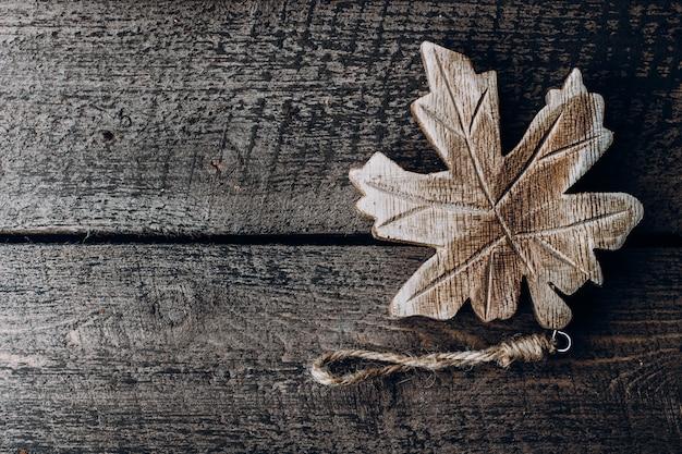 Feuille d'érable en bois sur un fond en bois. symbole du canada. vue de dessus, espace de copie Photo Premium