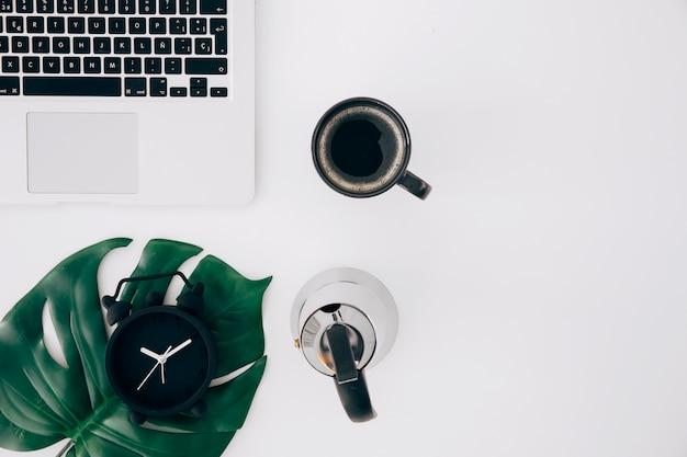 Feuille de monstre au réveil; bouilloire; tasse à café et ordinateur portable sur fond blanc Photo gratuit