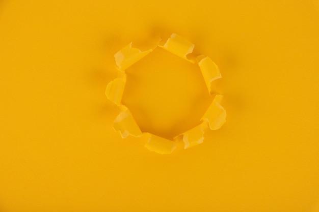 Une Feuille De Papier Jaune Avec Un Trou Au Milieu. Fond, Texture. Copiez L'espace. Photo Premium