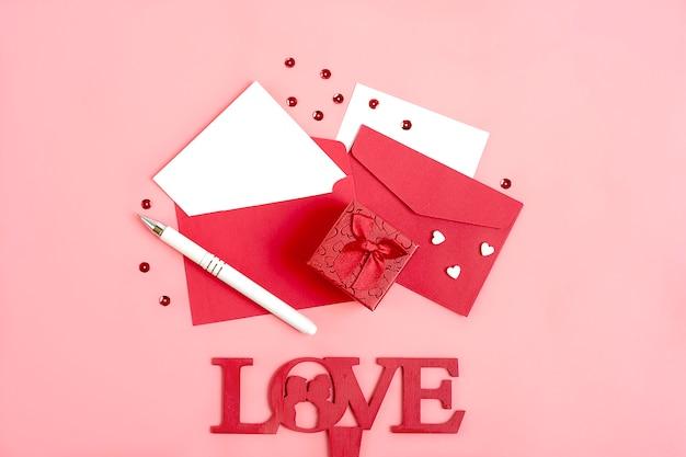 Feuille de papier pour le message, enveloppe rouge, boîte-cadeau, étincelles, crayon bonne fête de la saint-valentin Photo Premium