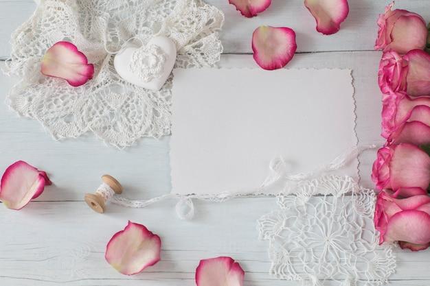 Une feuille de papier, des roses roses, des pétales de roses et des dentelles Photo Premium