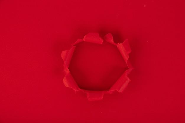 Une Feuille De Papier Rouge Avec Un Trou Au Milieu. Rappel. Fond, Texture. Copiez L'espace. Photo Premium