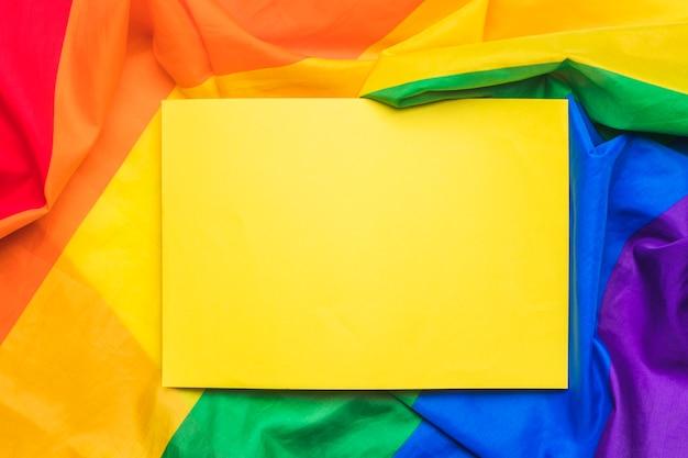 Feuille de papier vide jaune sur drapeau lgbt froissé Photo gratuit