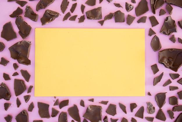 Feuille de papier vierge avec du chocolat fissuré sur la table Photo gratuit
