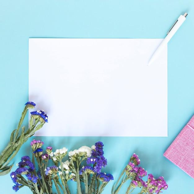 Feuille de papier vierge; stylo et bouquet de fleurs colorées sur fond bleu Photo gratuit