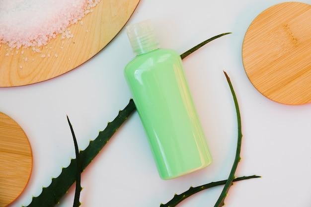 Feuilles d'aloe vera avec une bouteille de crème de beauté Photo gratuit