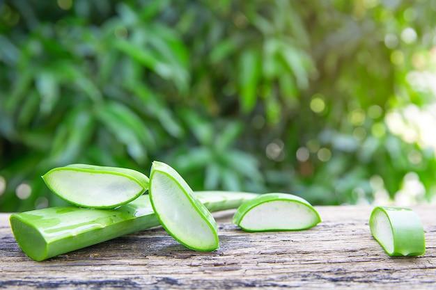 Feuilles d'aloe vera fraîches et des tranches sur une table en bois. Photo Premium