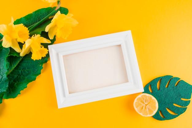 Feuilles artificielles; fleurs de jonquille; citron près du cadre blanc sur fond jaune Photo gratuit