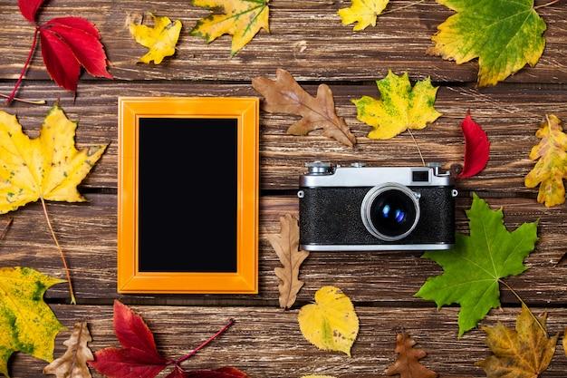 Feuilles d'automne, caméra et cadre sur une table en bois. Photo Premium