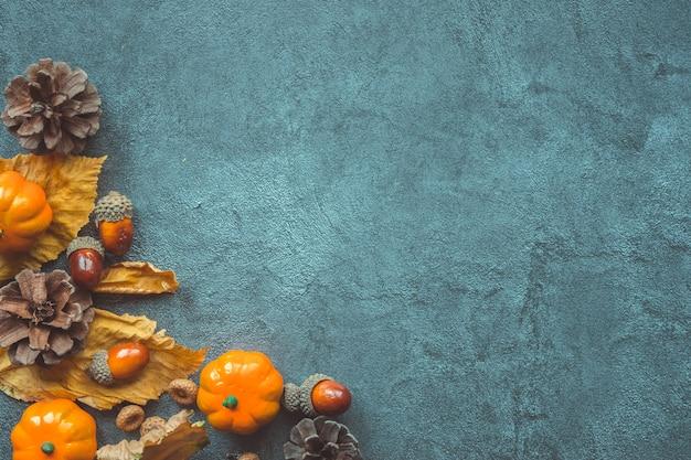 Feuilles d'automne, citrouilles décoratives, glands et cônes sur fond gris Photo Premium