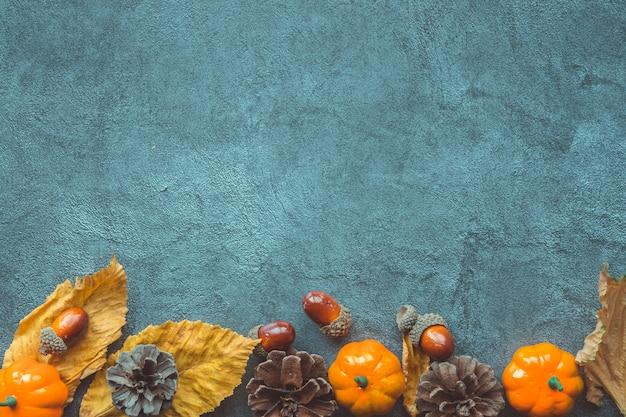 Feuilles d'automne, citrouilles, glands et cônes décoratifs sur fond en bois bleu Photo Premium