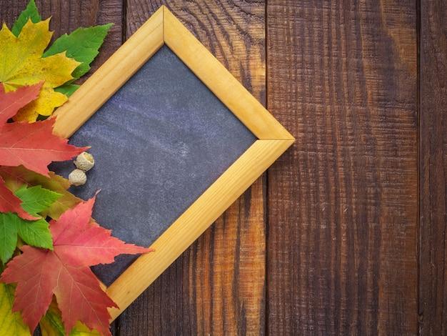 Feuilles d'automne colorées avec cadre en bois pour texte sur un bois texturé Photo Premium