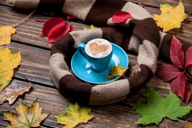 Feuilles d'automne, écharpe et tasse à café sur la table en bois. Photo Premium