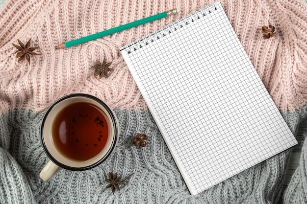 Feuilles D'automne Jaunes, Une Tasse De Thé Et Un Cahier Sur Un Pull Texturé Photo Premium