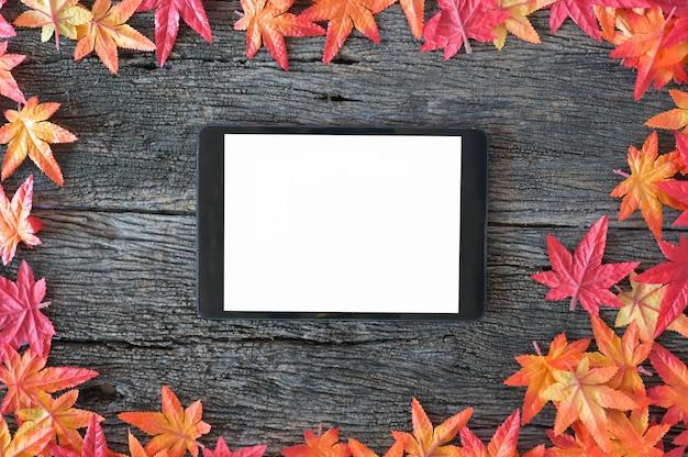 Feuilles d'automne et maquette tablette numérique sur fond de nature en bois avec espace de copie. Photo Premium