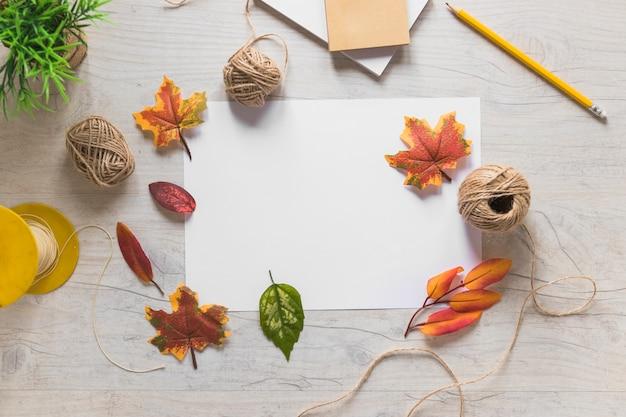Feuilles d'automne sur papier blanc et bobine de fil sur la table en bois Photo gratuit