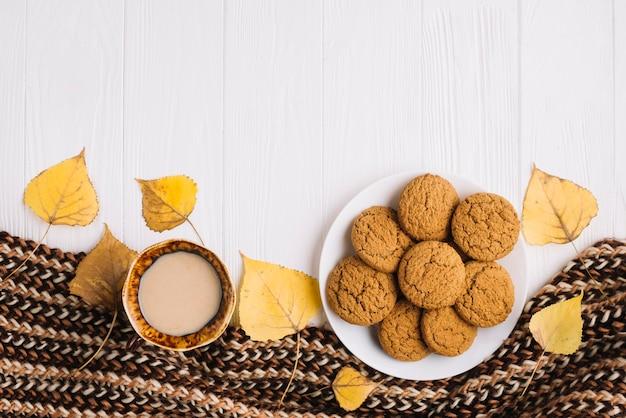 Feuilles et écharpe près des biscuits et des boissons Photo gratuit