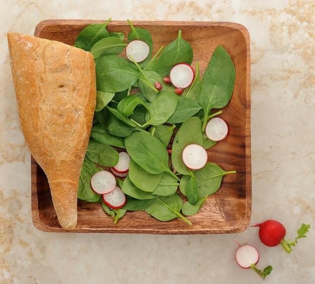 Feuilles d'épinards, œufs, radis et graines de grenade Photo Premium